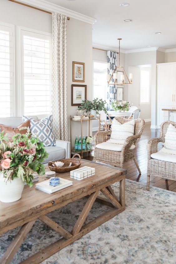 a modern country living room in neutrals, with a creamy sofa, woven chairs, a low coffee table, printed textiles and potted plants