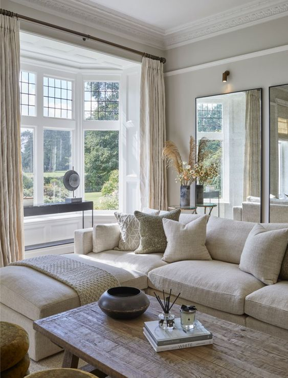 a modern country living room in neutrals, with mirrors, a creamy sectional, a bay window, a wooden table and cool textiles