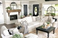 a modern country living room with a fireplace, chic neutral furniture, printed pillows, a wooden mantel and potted plants