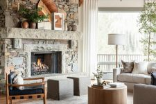 a modern country living room with a fireplace clad with faux stone, wooden beams, neutral furniture and a round coffee table