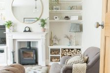 a modern country living room with a hearth, a grey sofa and an ottoman, a leather sofa, firewood, built-in shelves and potted plants