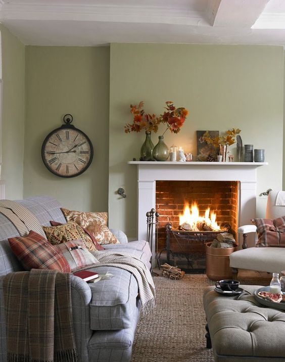 a modern country living room with light green walls, a fireplace, neutral furniture and printed textiles, a vintage clock and leaves