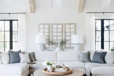 a modern country living room with wooden beams on the ceiling, neutral furniture, printed pillows and a round table is welcoming