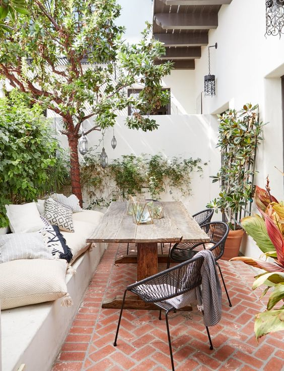 a modern country patio with a birck floor, a built-in bench, a vintage wooden table, some wicker chairs and potted plants and trees
