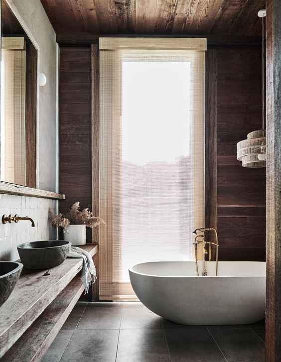 a modern country style bathroom with stained walls and a ceiling, a large wall-mounted vanity, stone sinks and a lovely bathtub