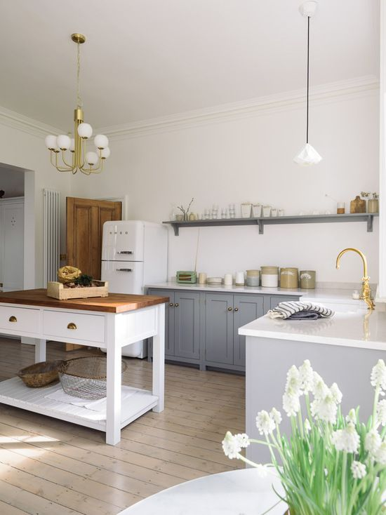 a modern country style kitchen with grey cabinets and a white kitchen island, pendant lamps and touches of gold