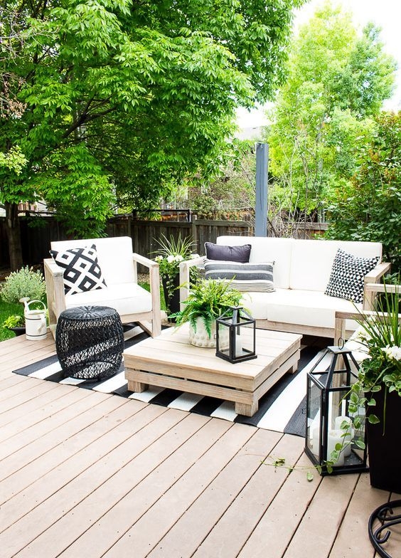 a modern country terrace with a deck, simple wooden furniture and printed textiles, a black side table and candle lanterns and greenery