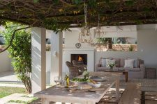 a modern country terrace with a living roof over the space, a whitewashed dining set with benches and an outdoor living room by the fireplace