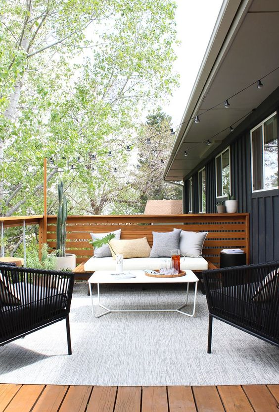 a modern country terrace with a wooden deck, a large rug, a sofa, rattan chairs, a small table and potted plants and cacti
