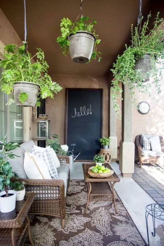 a modern country terrace with woven furniture, potted greenery, printed textiles and a chalkboard is a lovely and welcoming space