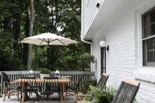 a modern country terrace with woven loungers, a wooden trestle table, black chairs and potted greenery plus an umbrella over the dining space