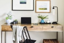 a modern country work station with a black vintage chair, a basket with a lid, a small gallery wall and some greenery