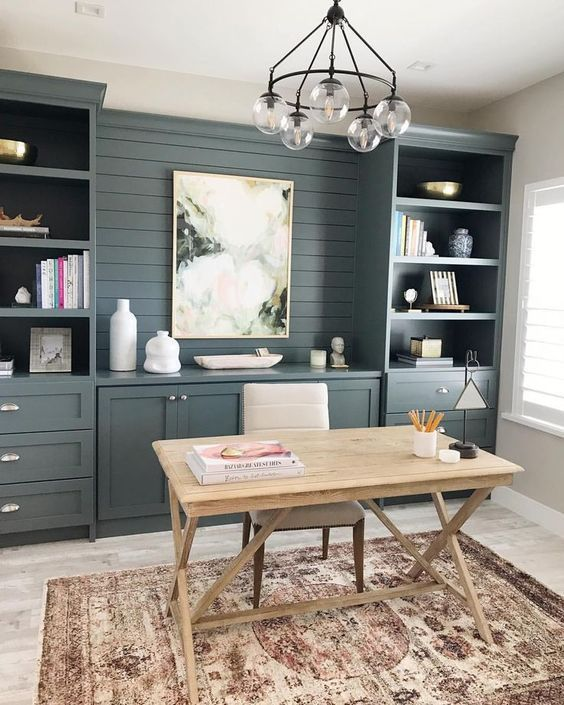 a modern country working space with slate grey storage units that are built in, a wooden trestle desk and a chandelier plus a boho rug