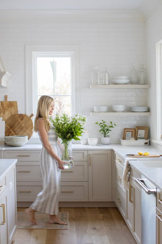 a modern creamy country style kitchen with shaker cabientry, white countertops and walls clad with white subway tiles plus open shelves