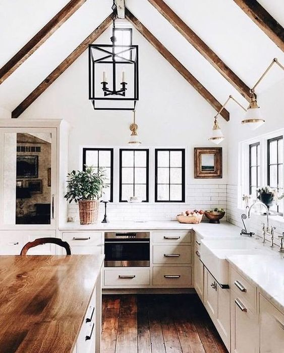a modern dove grey country kitchen with dark wooden beams on the ceiling, pendant lamps and a kitchen island with a butcherblock countertop