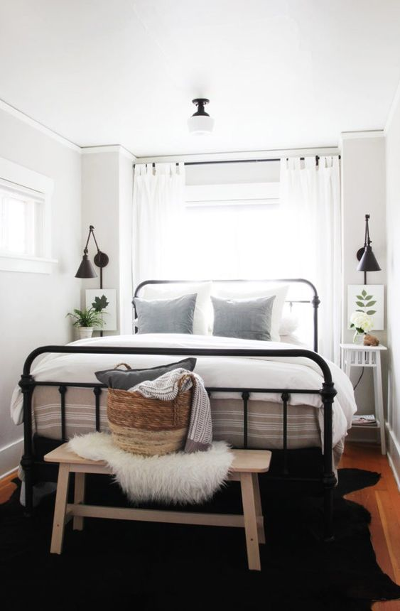 a modern farmhouse bedroom with a black forged bed, neutral nightstands and a bench, neutral bedding and a lovely basket