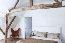 a modern farmhouse bedroom with stained wooden beams that highlight the attic ceiling, a neutral bed with a bench and a leather chair