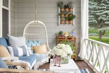 a modern farmhouse coastal porch with wicker furniture, a suspended egg-shaped chair, a coffee table, striped accessories, potted plants