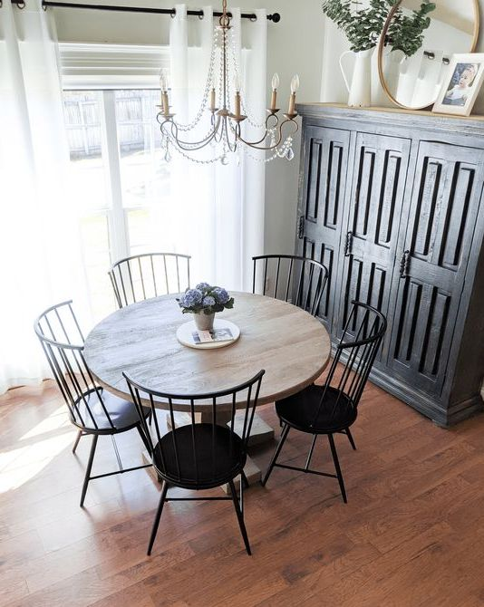 a modern farmhouse dining nook with a black storage unit, a stained round table, black chairs and a crystal chandelier
