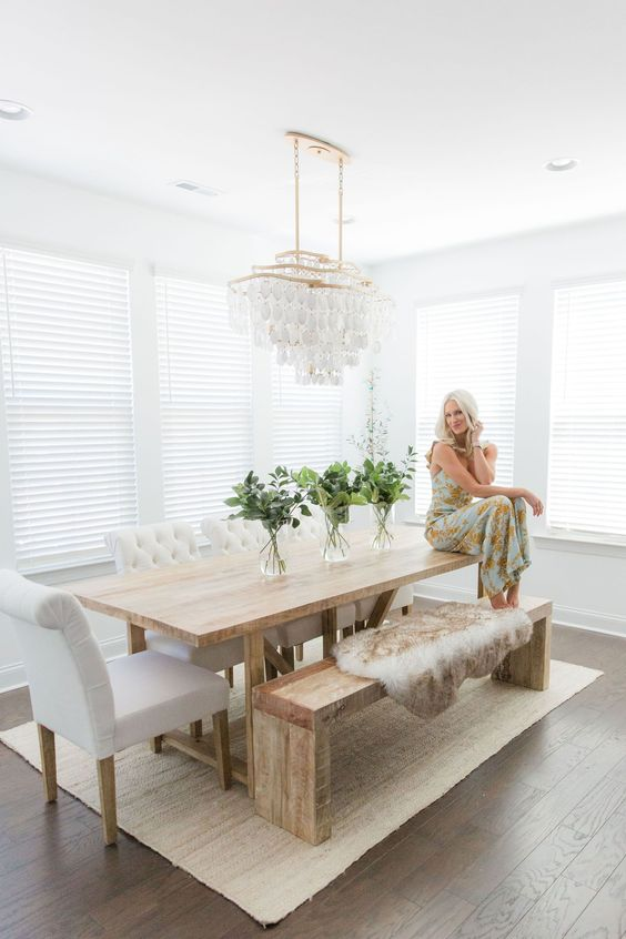 a modern farmhouse dining room with a bit of glam, a stained table and a bench, upholstered chairs and a crystal chandelier