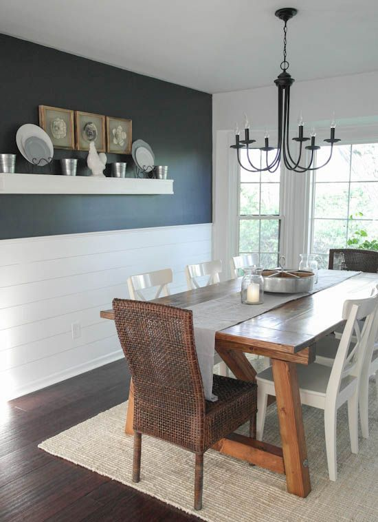 a modern farmhouse dining room with a black wall and white planks, a stained dining table, mismatching chairs and a vintage chandelier