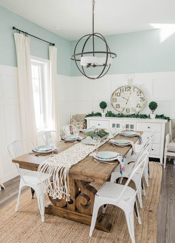 a modern farmhouse dining room with blue and white paneled walls, a stained vintage dining table, white metal chairs, a sphere chandelier