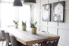 a modern farmhouse dining space with a grey paneled accent wall, a dining table with a thick tabletop, mismatching chairs and blakc pendant lamps