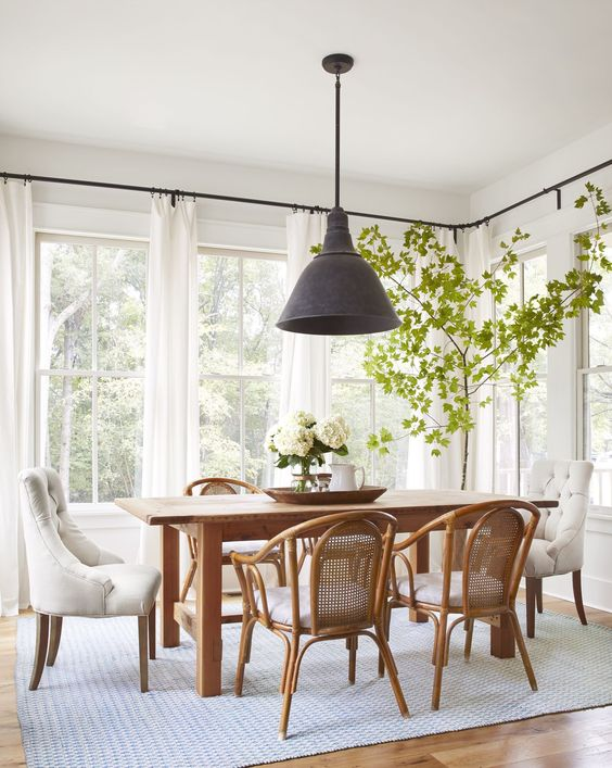 a modern farmhouse dining space with a stained table, woven and upholstered chairs, a potted tree, a black pendant lamp