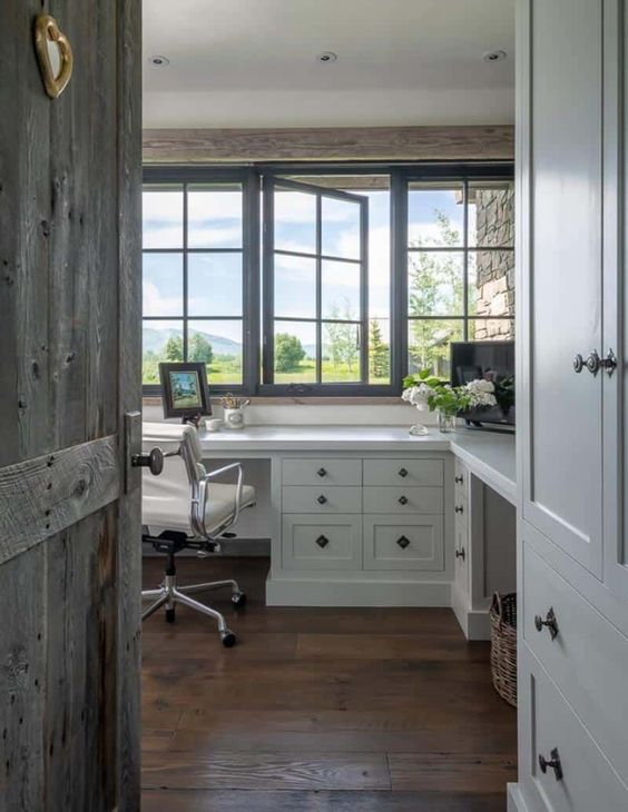 a modern farmhouse home office with French windows, a white shared desk, a leaher chair and wooden beams