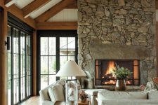 a cozy living room with a large stone fireplace
