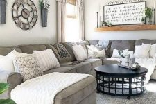 a modern farmhouse living room with a grey sectional, an open shelf, some wall decor and neutral and printed pillows