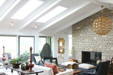 a modern farmhouse living room with a stone clad fireplace, neutral and dark furniture, a console and a bench plus a gilded lamp
