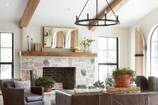 a modern farmhouse living room with a stone clad fireplace, wooden beams, leather furniture, a metal chandelier and potted plants