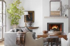 a modern farmhouse living space with a fireplace, neutral furniture, wooden coffee tables, wooden beams on the ceiling and a potted tree