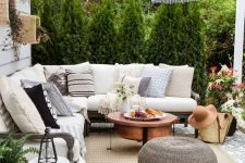 a modern farmhouse patio with a roof, a sectional, a copper coffee table, a woven ottoman, a pendant lamp and some plants