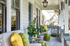 a modern farmhouse porch styled for summer, with simple wooden furniture, bright pillows, bold green side tables and potted trees