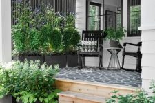a modern farmhouse porch with a black printed rug, black rockers and printed pillows, potted plants and blooms is very cozy
