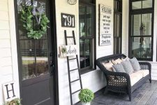 a modern farmhouse porch with a black wicker sofa with lots of pillows, a ladder, some signs and a greenery wreath