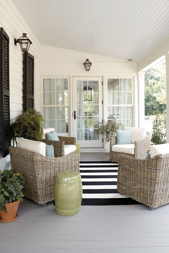 a modern farmhouse porch with elegant wicker chairs and pillows, potted greenery and blooms, a side table and cool lanterns