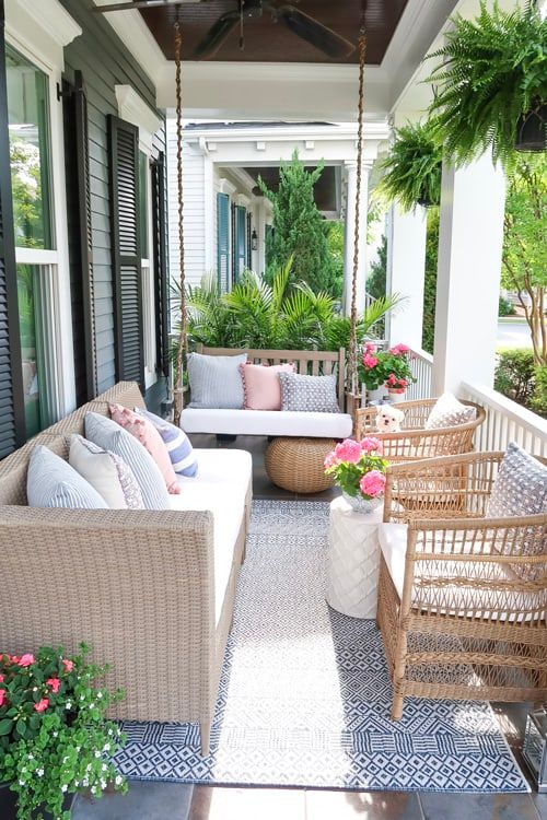 a modern farmhouse porch with wicker furniture, printed pillows, a suspended bench, potted blooms and greenery is welcoming