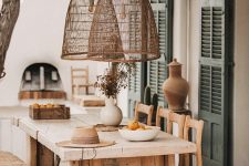a modern farmhouse terrace with a roof and woven lamps, with a rough wood dining set and a hearth is a lovely space to have a meal