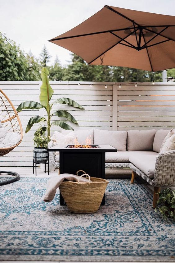 a modern farmhouse terrace with a wicker sectional, a fire pit, a rattan chair, an umbrella, potted plants is a lovely space