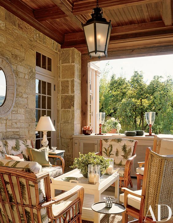 a modern farmhouse terrace with rattan chairs and small rables, pritned textiles, candle lanterns and some potted greenery