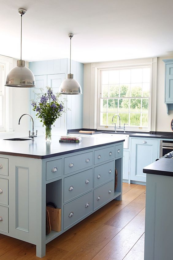 a modern light blue country kitchen with dark countertops, pendant lamps and large windows plus a lovely hardwood floor is chic