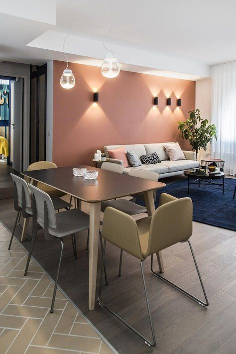 a modern living and dining space with a mauve accent wall, a white sofa, some coffee tables and a chic dining zone with mismatching chairs
