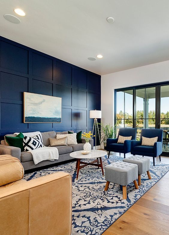 a modern living room with a navy paneled wall, chic grey and navy furniture, a tan sofa, a printed rug and blankets