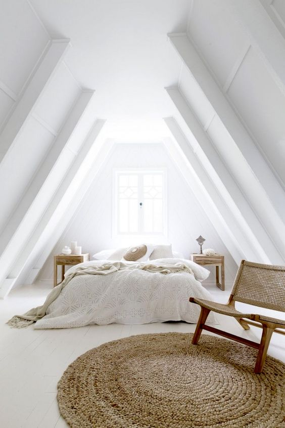 a modern neutral country bedroom with an attic ceiling, done in white and creamy shades, with wooden and rattan furniture and a jute rug
