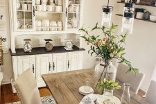 a modern neutral dining room with a neutral buffet, a stained table, upholstered chairs, a vintage ladder with bulbs