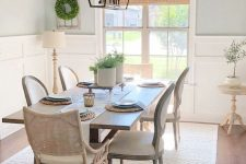 a modern neutral dining space with white paneling, a stained trestle dining table and mismatching chairs, a metal chandelier and greenery