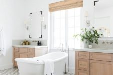 a modern rustic bathroom with a lovely patterned tile floor, stained vanities, a basket and shades plus a vintage-inspired tub